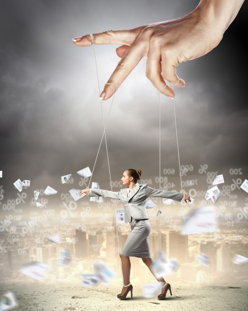 Businesswoman marionette on ropes controlled by puppeteer against documents picture