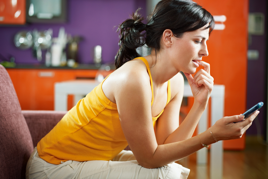 mid adult woman on sofa staring at her mobile phone and biting nails. Horizontal shape, waist up, copy space